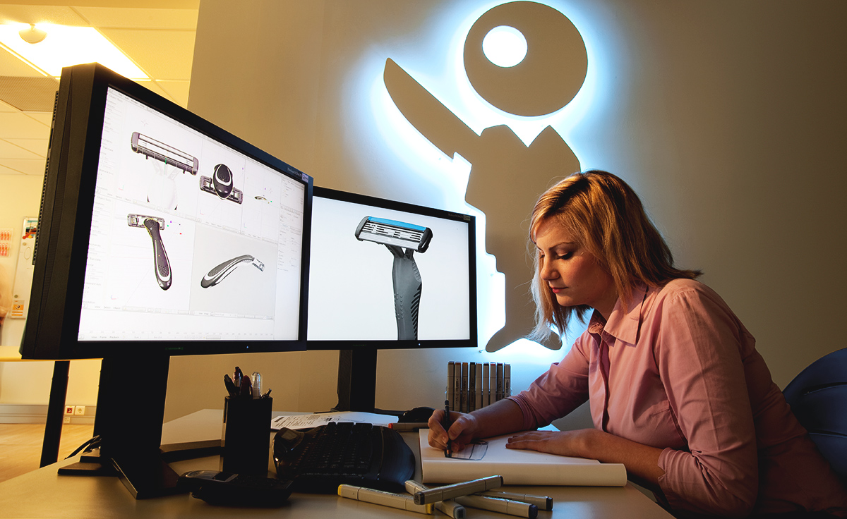 woman working on a double screen computers with razors images in it