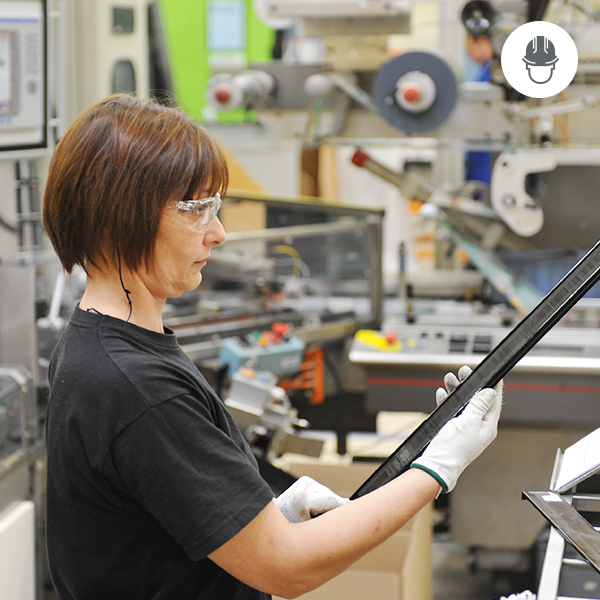 woman in workplace wearing safety glasses and gloves