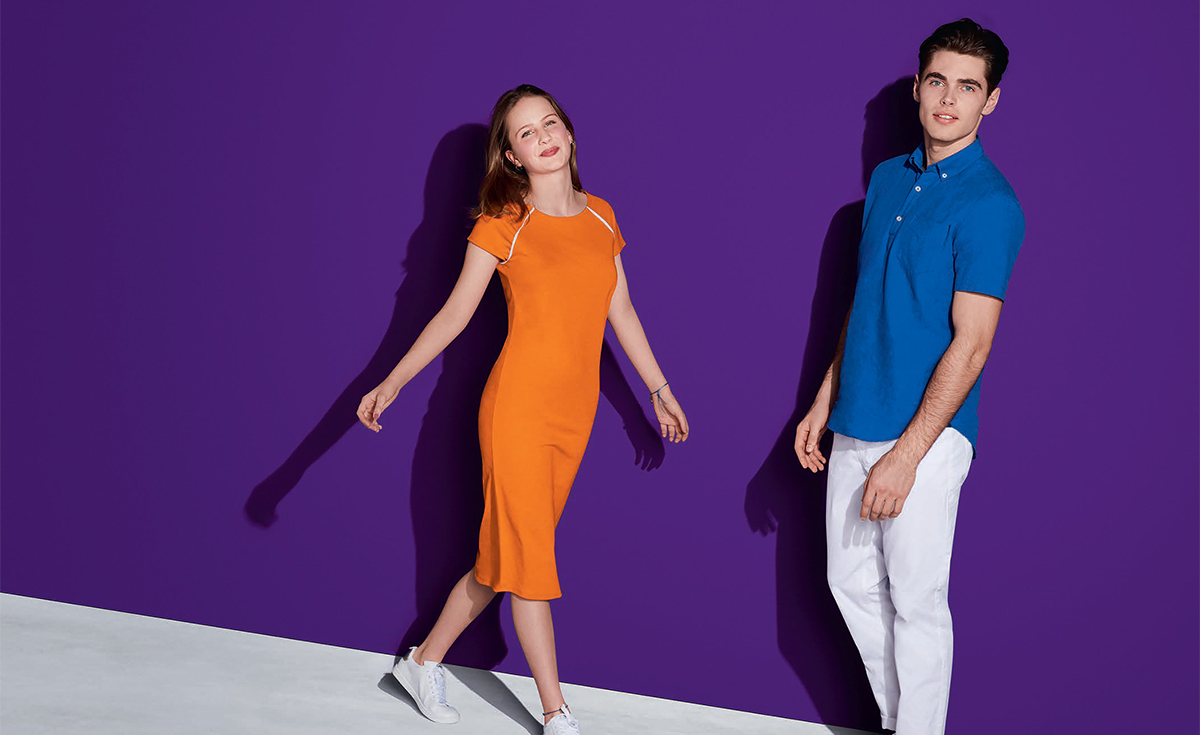 a girl and a boy standing on a purple background